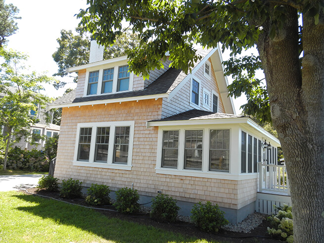 Side view of exterior of Cape Cod cottage with new wood windows