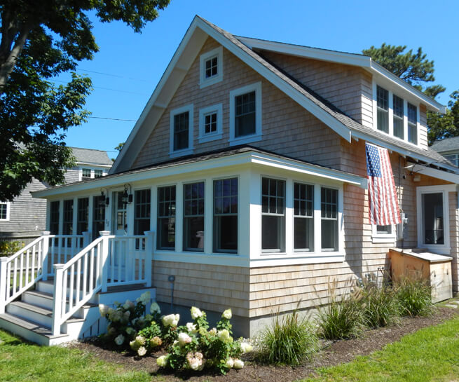 Front entrance of a cottage in Cape Cod, MA, with new wood windows