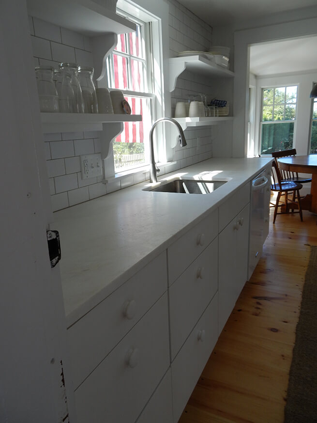 New wood window with white trim above kitchen sink in Cape Cod cottage