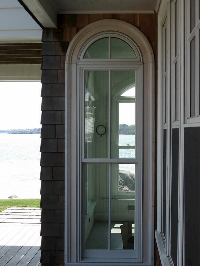 Wood double-hung window with special-shape transom on a shingle-style home
