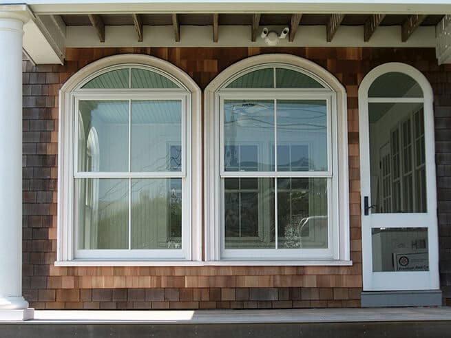 Two wood double-hung windows with special shape transoms on a shingle-style home