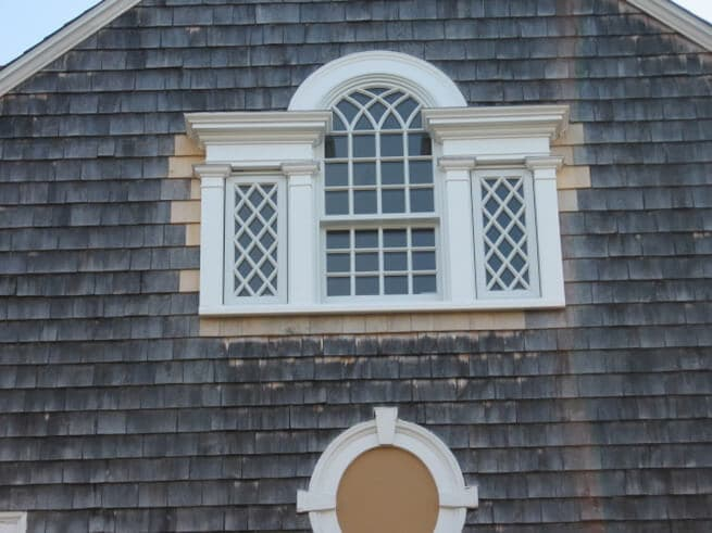 Exterior view of new wood window on shingle-style home