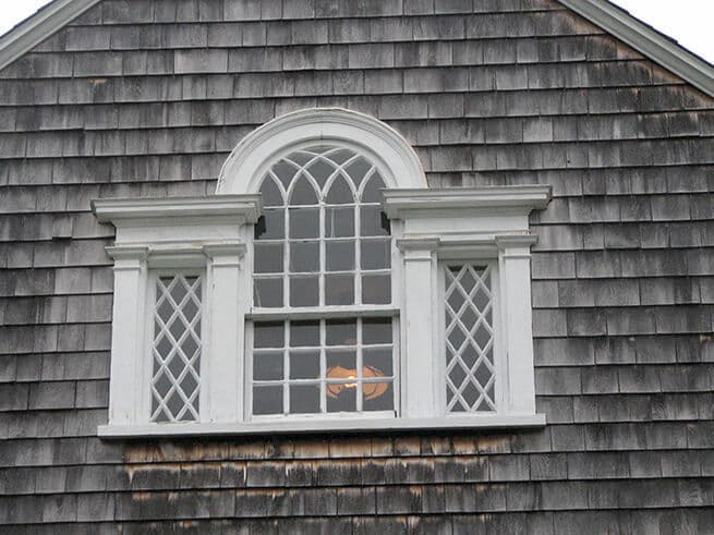 Exterior view of old wood window on shingle-style home