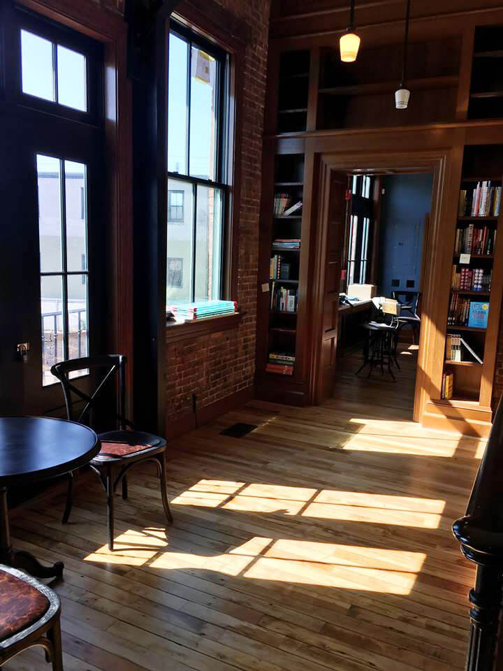 Sunlight comes through new wood windows on the storefront of Savoy Bookstore