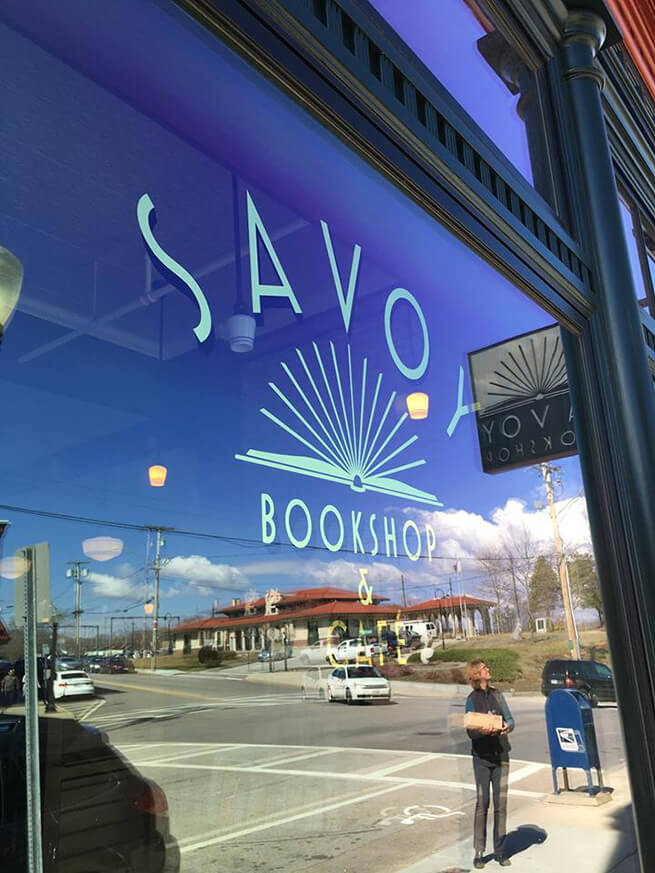 Close-up of large wood storefront window on Savoy Bookstore