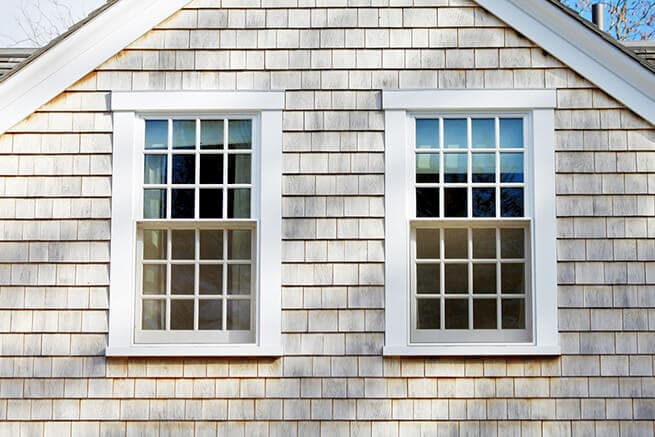 Exterior view of wood double-hung windows on a shingle-style home