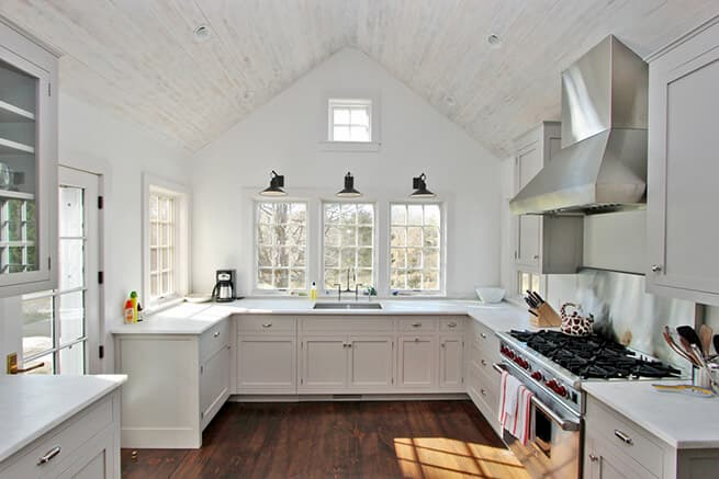 White kitchen with wood casement windows with traditional grille patterns