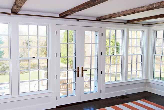 Interior view of wood double-hung windows and double hinged French patio doors