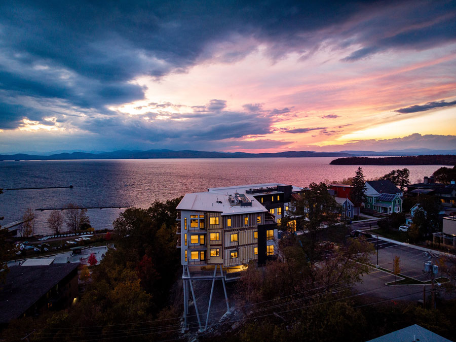 Front of One Lakeview Apartments in Burlington, Vermont, with new windows lit up at dusk
