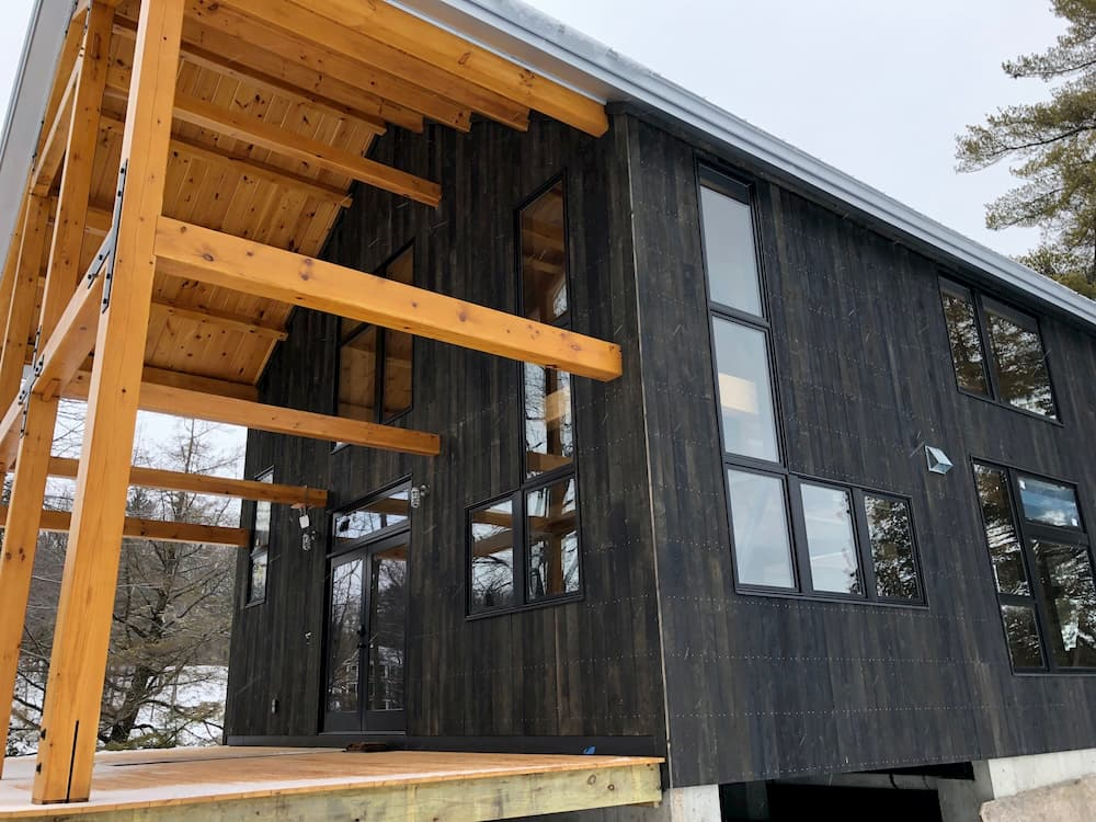 Exterior view of contemporary home with black-clad wood windows
