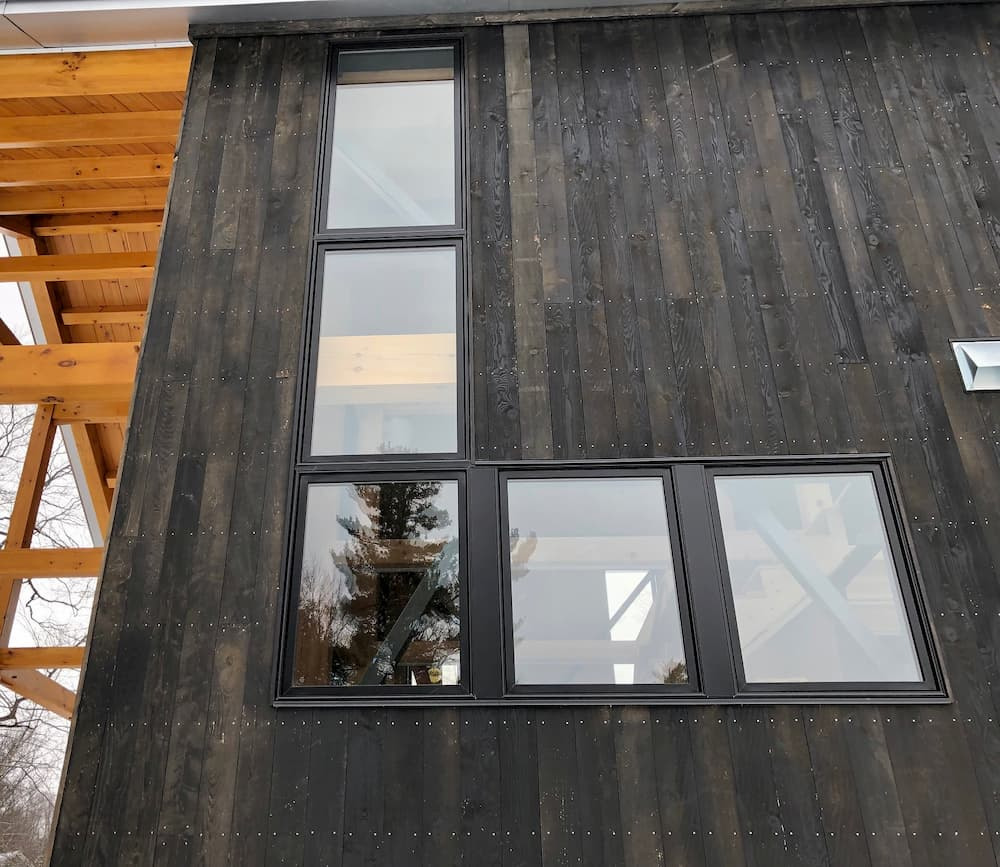 Exterior view of cabin with black-clad wood windows