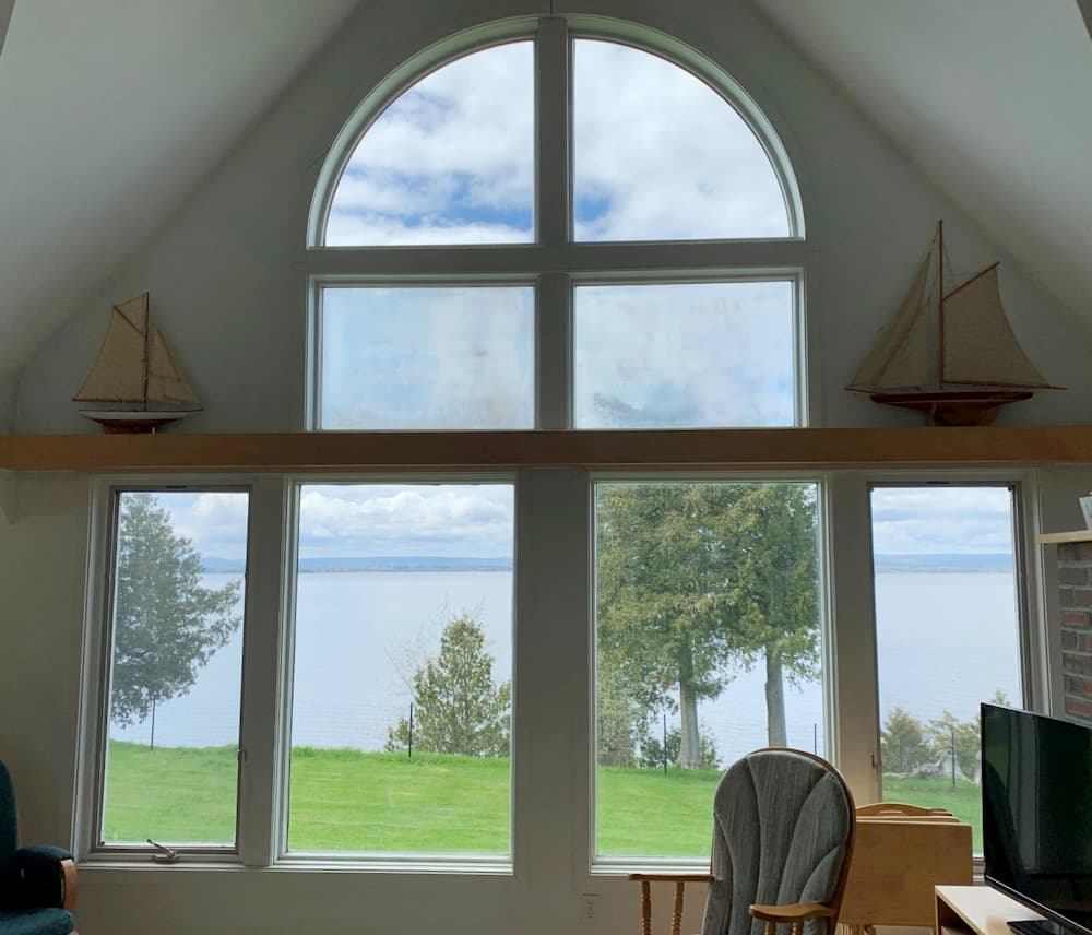 Interior view of multiple picture windows looking out onto Lake Champlain