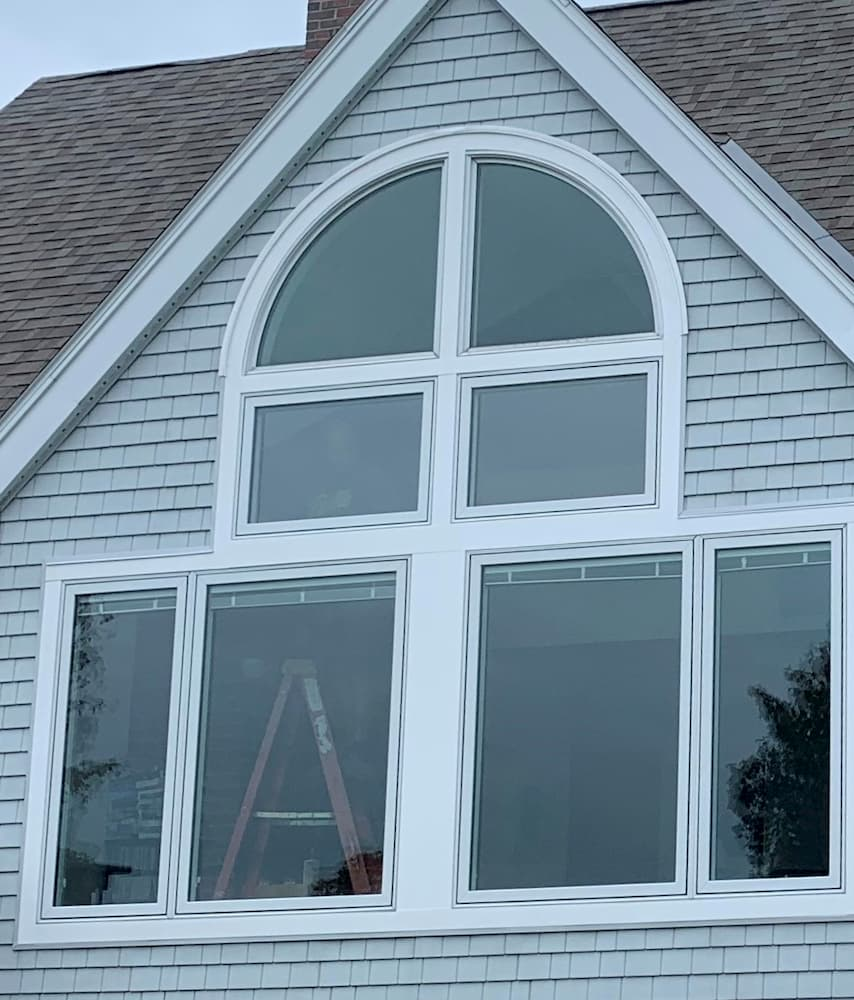 Exterior view of new wood special shape, fixed and casement windows with white trim