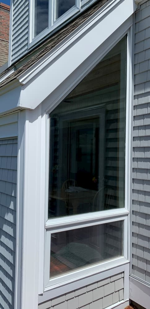 Exterior view of special shape and awning window on a shingle-style home