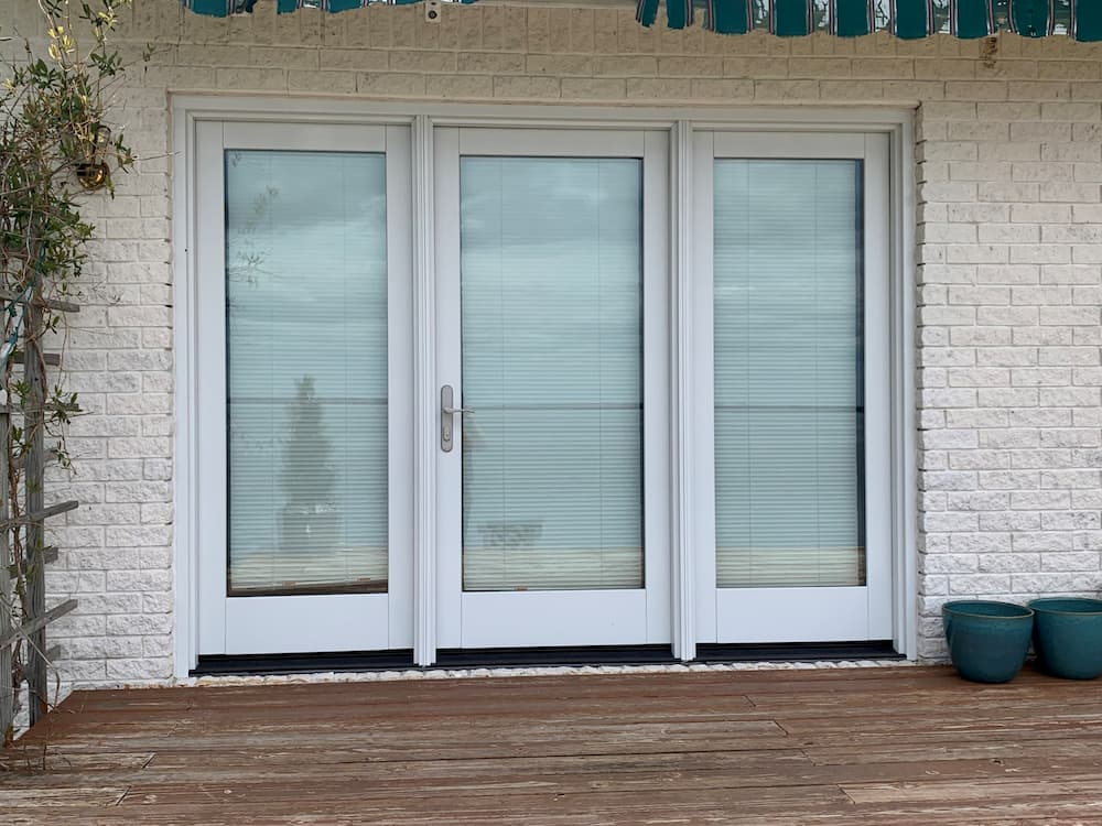 Three-panel hinged French patio door replacement with white trim