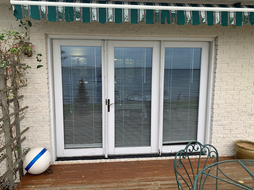 Three-panel hinged French patio door with white trim