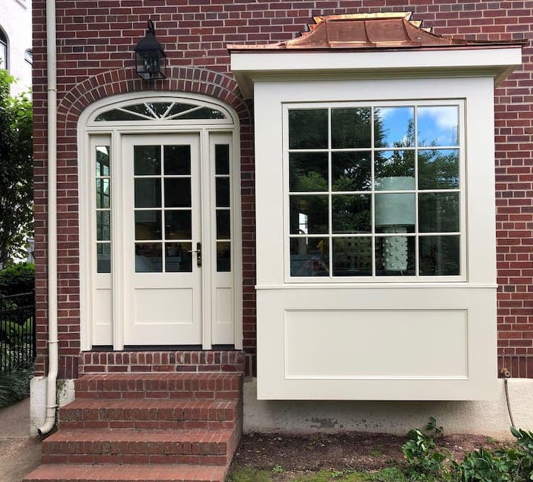 New wood door and fixed window with traditional grille pattern and white finish on red brick home