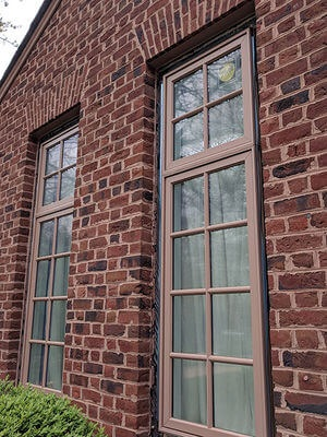 casement wood windows with custom color on brick house