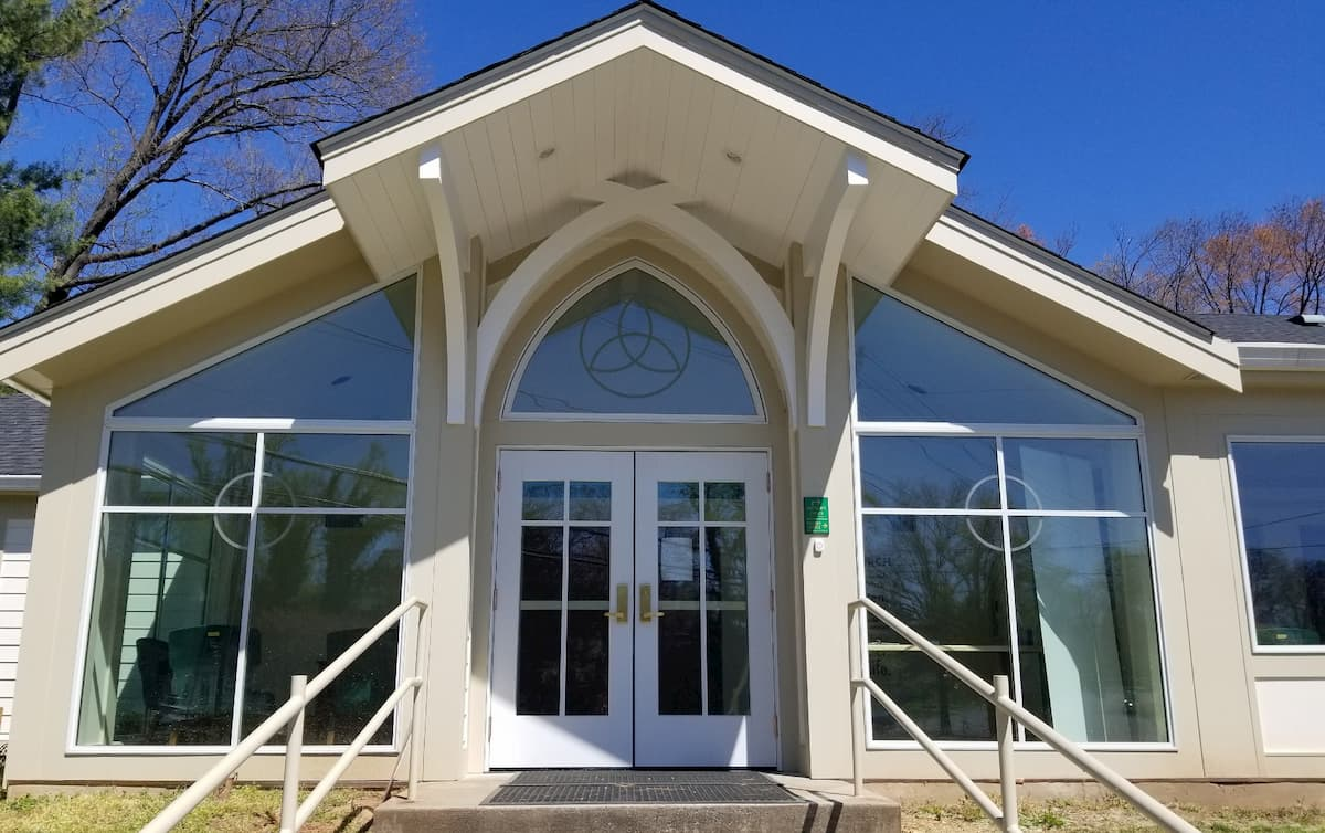 Front exterior view of a church with new double wood entry doors and custom windows