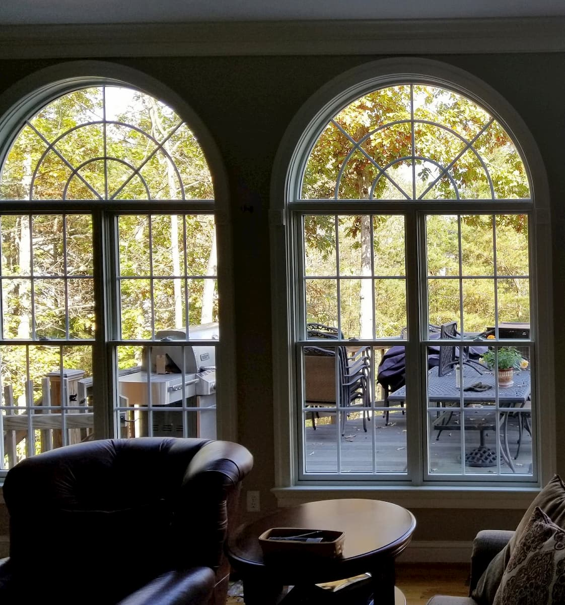 Interior view of wood double-hung windows with half-circle transoms and traditional grilles