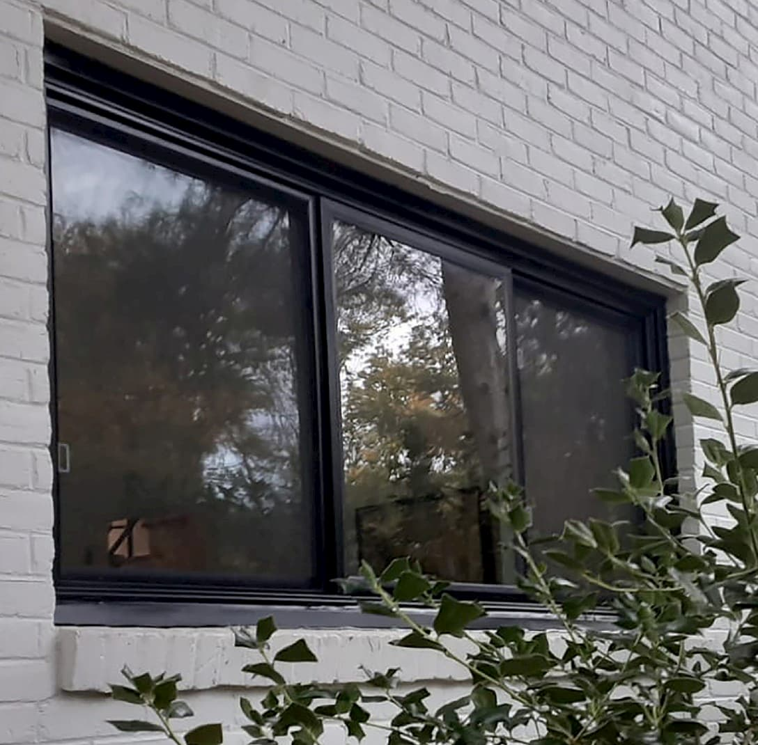 exterior view of black sliding fiberglass window on gray painted brick home