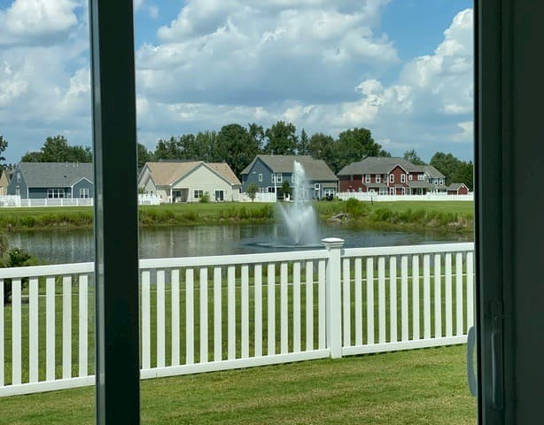 View through sliding glass door to nearby lake and fountain