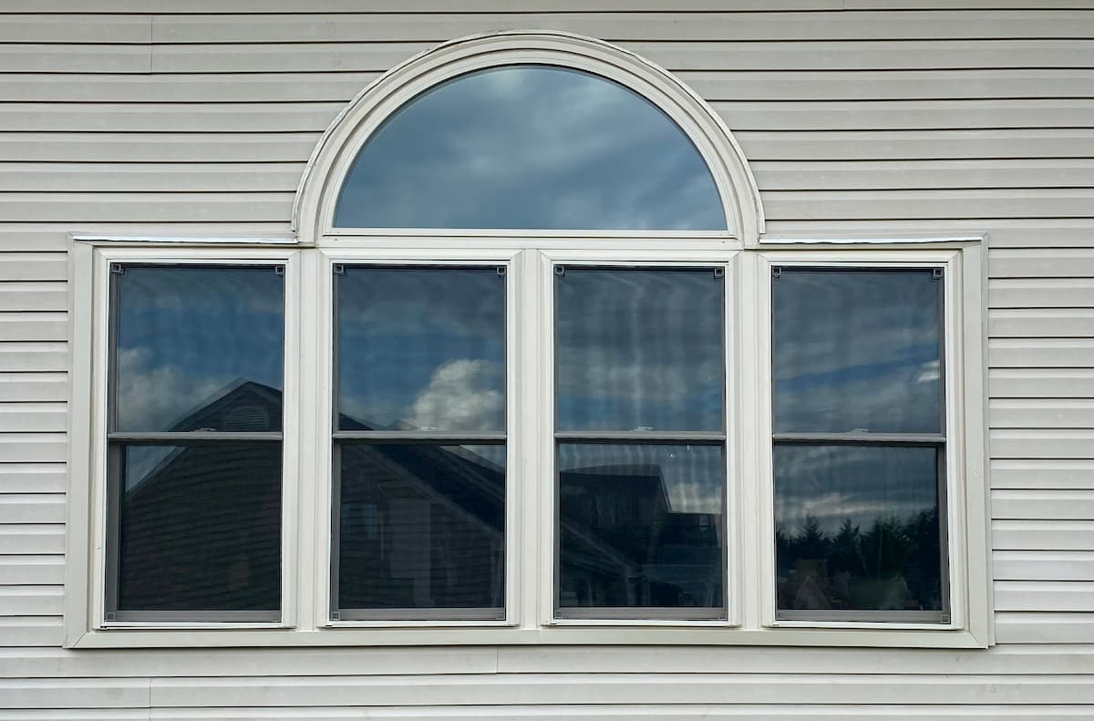 Exterior view of four vinyl double-hung windows with a half-arch transom.