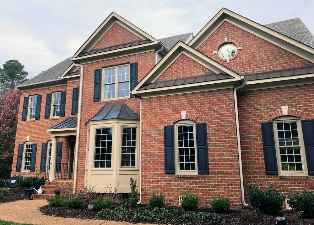 Front exterior view of red brick home with new wood double-hung windows