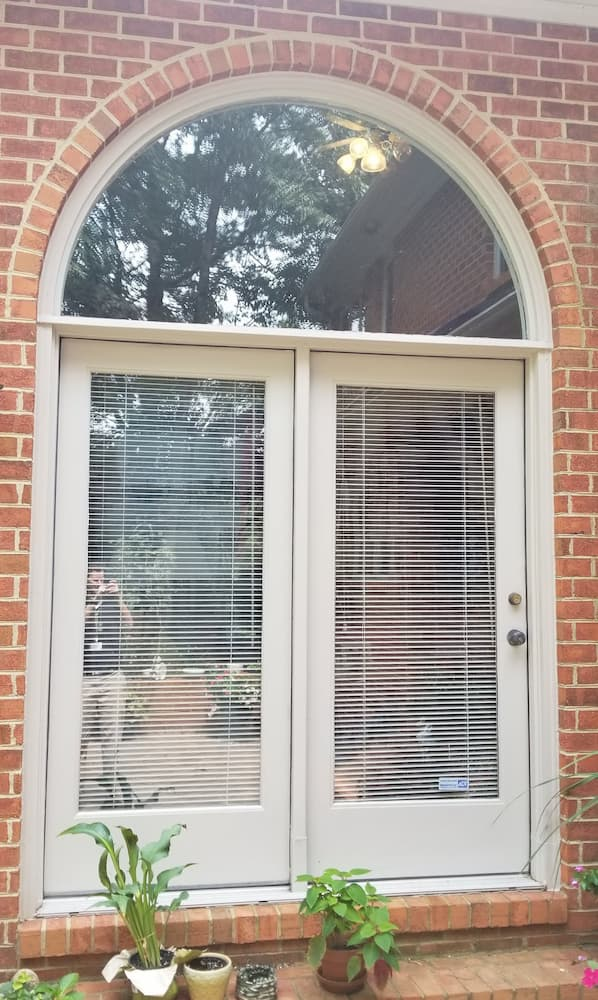 Old double patio doors on red brick home