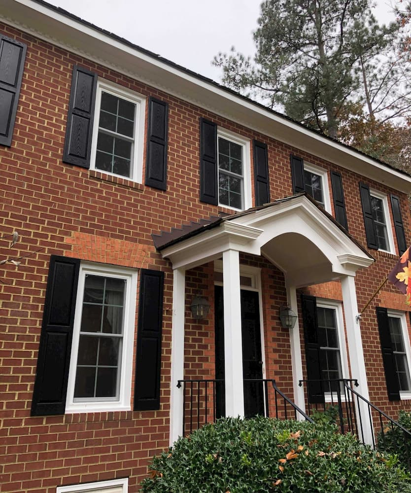 Exterior view of front entry of red brick home with new white vinyl double-hung windows