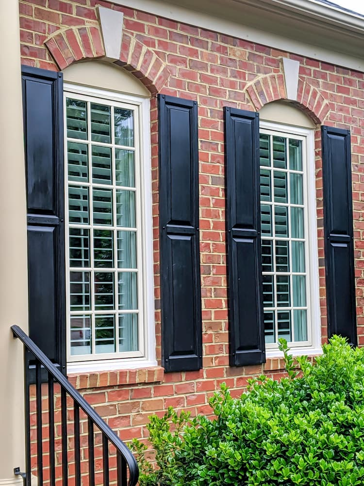 New wood windows with traditional grille pattern on a red brick home