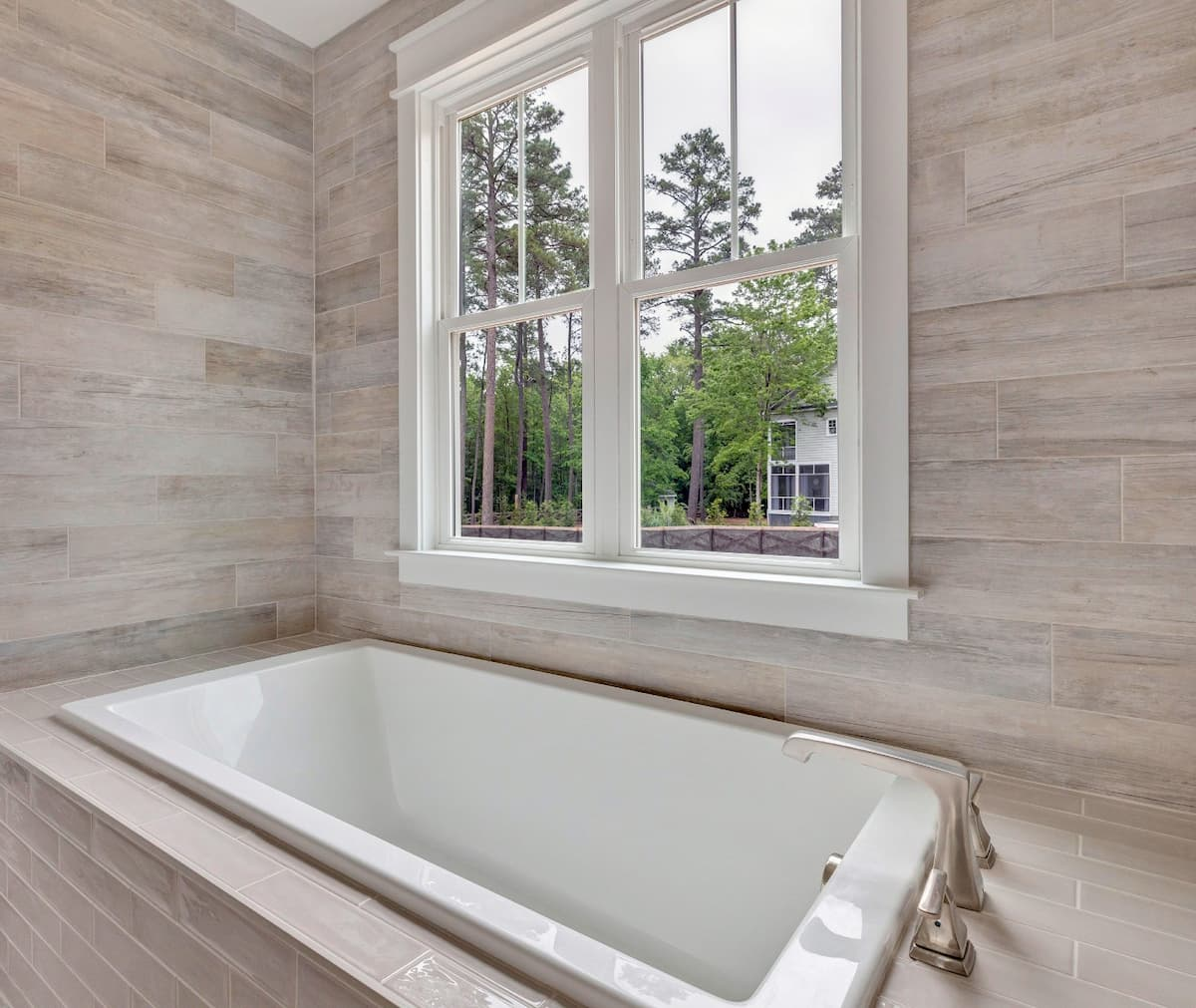 Interior view of two white wood double-hung windows in a bathroom.