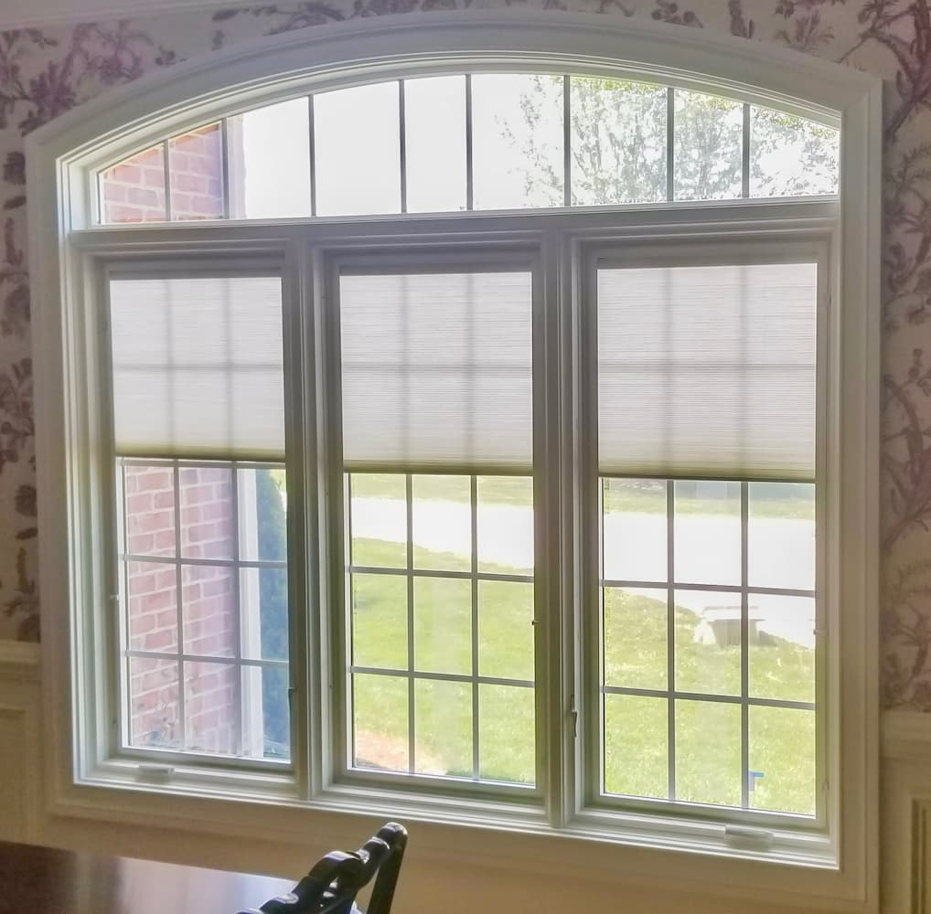Three wood casement windows with traditional grille patterns topped with an arch window.