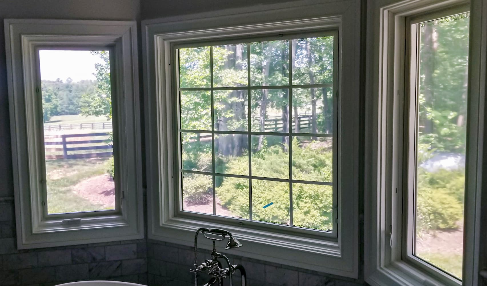 Two wood casement windows flanking a wood picture window with traditional grille pattern