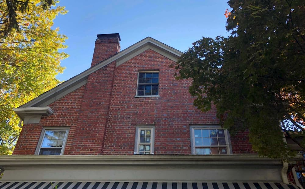 Exterior view of new wood double-hung windows on the second story of a red brick home