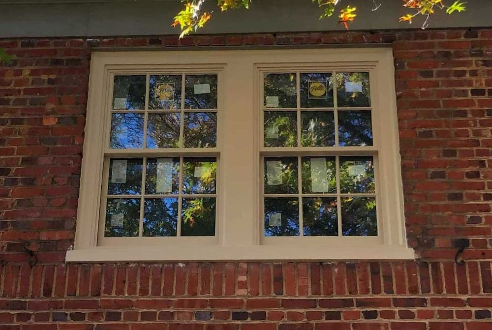 Exterior view of new wood double-hung windows on a red brick home