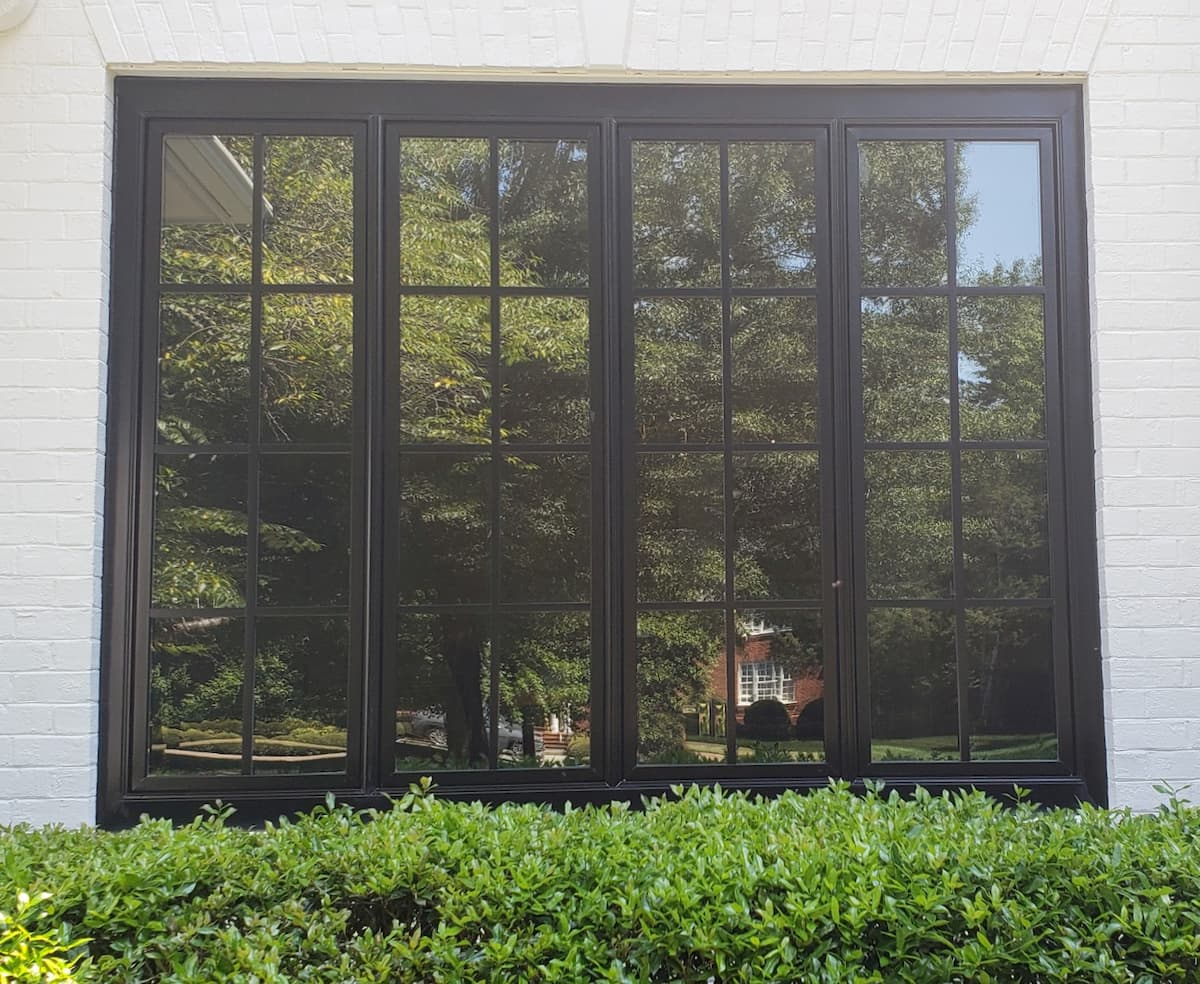 Four side-by-side black casement windows with traditional grille patterns