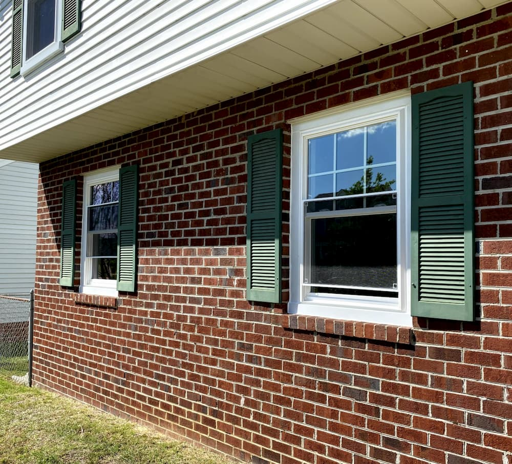 Two white double-hung windows on a red brick home