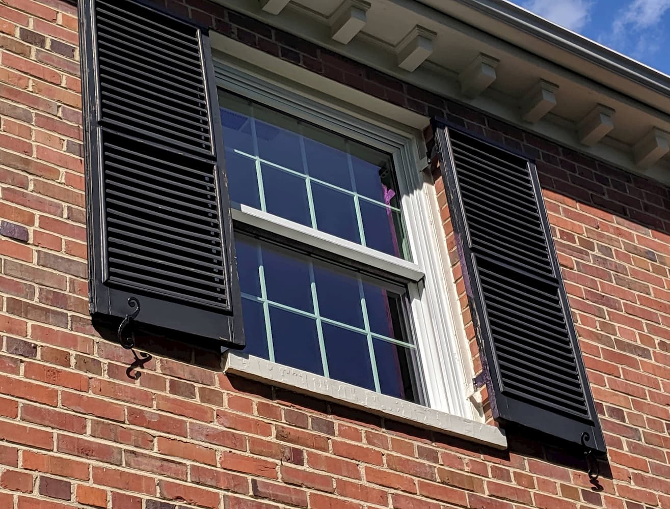 Wood double-hung window with traditional grille pattern on second story.