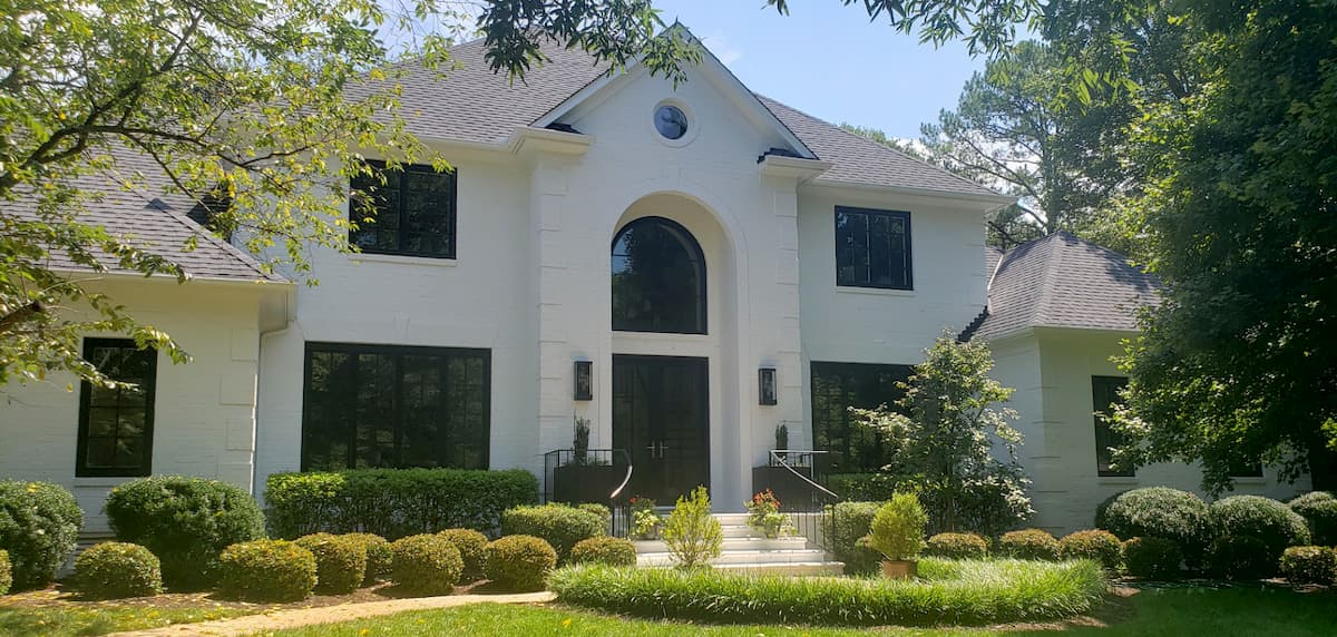 Painted white brick home with new black wood windows