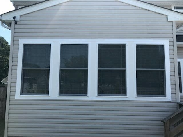 Exterior view of four fiberglass double-hung windows prairie-style grille patterns