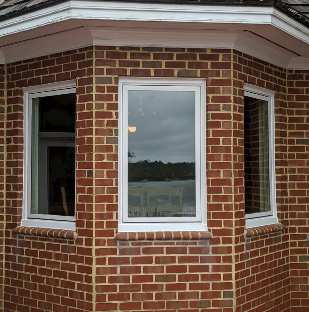 Exterior view of new white fiberglass casement windows on red brick home