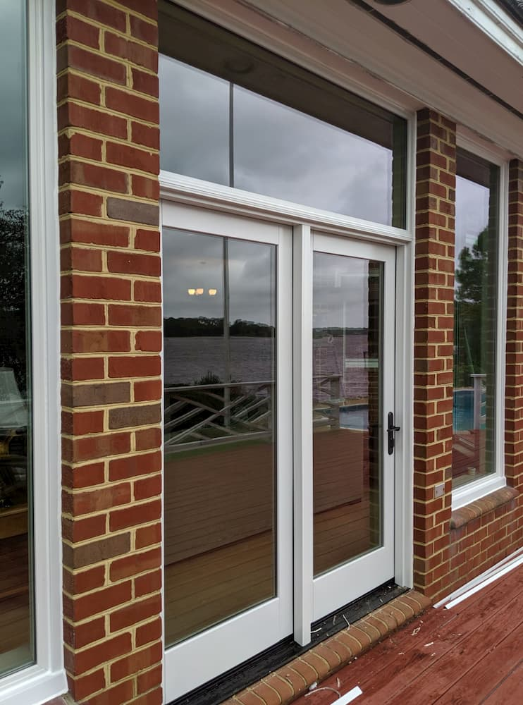 New fiberglass patio doors and windows on a red brick home