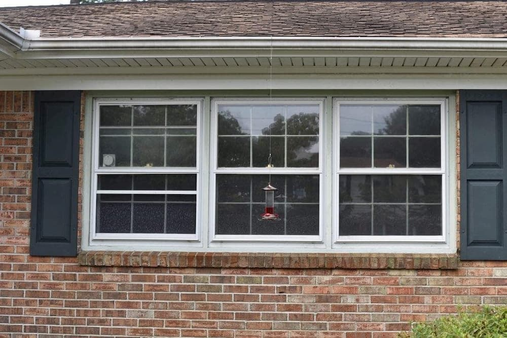 Old double-hung windows on red brick home