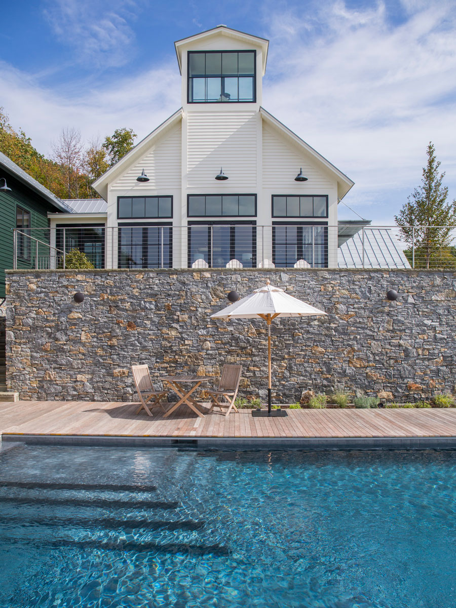 Poolside patio of home with black wood windows and patio doors in Williamstown, MA