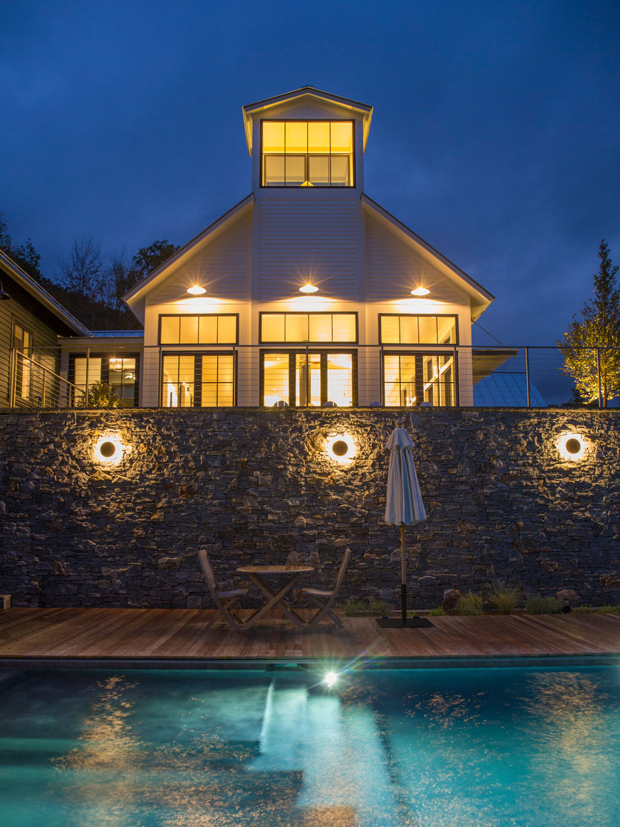 Poolside patio at night of home with black wood windows and patio doors in Williamstown, MA