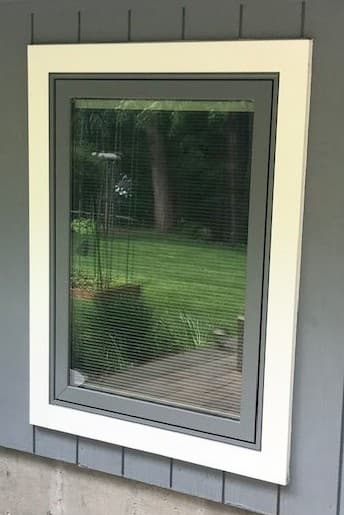 Close-up exterior view of new gray casement window with white trim on a gray home