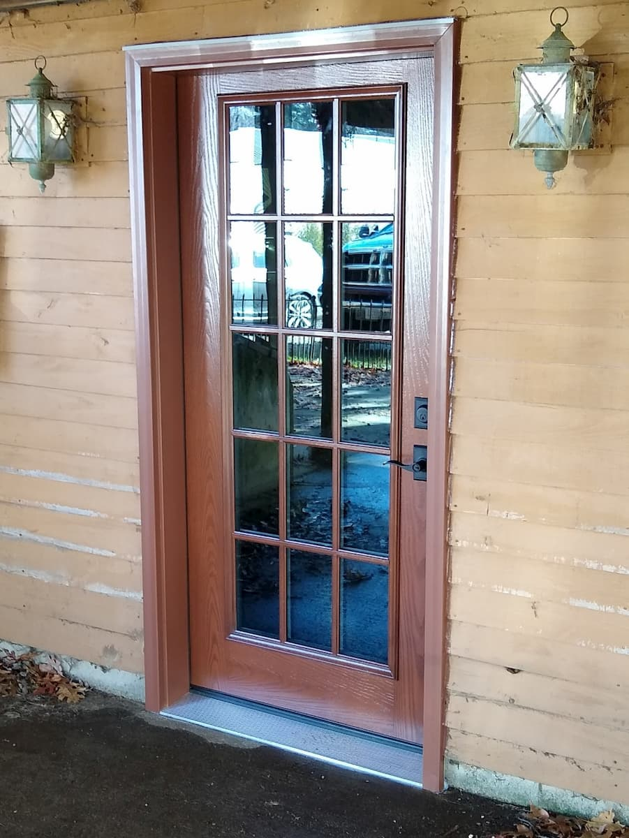 Exterior view of new fiberglass wood-look entry door.