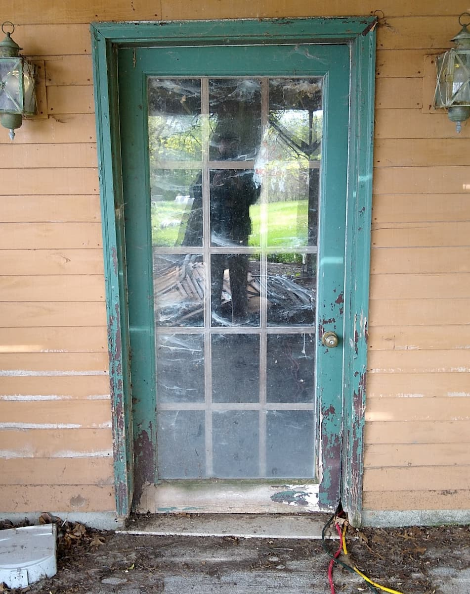 Exterior view of old, damaged basement door.