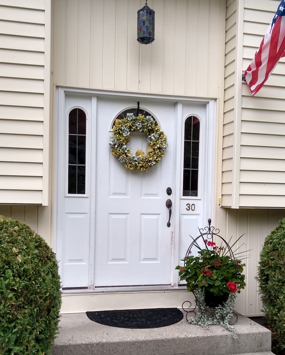 Exterior view of old white entry door with sidelights